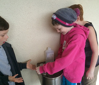 """Students collect water samples from the school drinking fountain to test for lead contamination for their project """"Is Our School Water Safe?"""""""