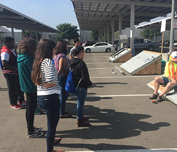 HS Students learning about photovoltaic cells on commercial structures
