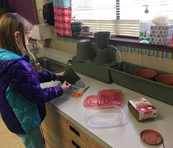 """A student works on the plant-based greywater filter the class built as part of their project, """"What Does it Take to Filter Greywater?"""""""
